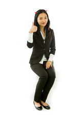 Asian young businesswoman sitting on stool in devil horns making