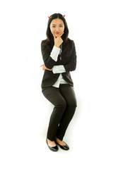 Happy Asian young businesswoman sitting on stool in devil horns