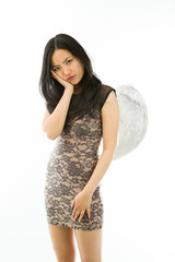 Upset Asian young woman dressed up as an angel with her hands on