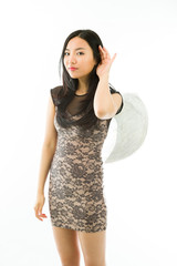 Asian young woman dressed up as an angel trying to listen