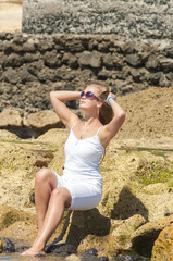 Blondy girl in white with sunglasses on the beach. Tenerife