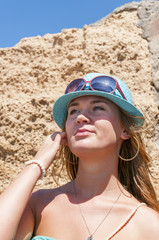 Blondy girl with sunglasses and hat on the beach. Tenerife