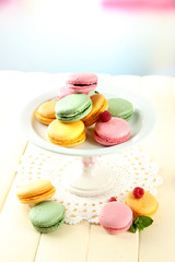 Gentle macaroons in vase on table on light background