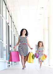 Happy mom and daughter with shop bags, outdoors