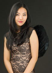 Portrait of an Asian young woman dressed up as a black angel