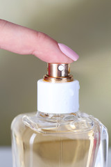 Bottle of perfume in hand on bright background