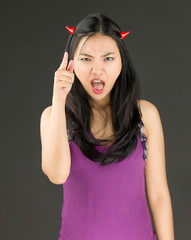 Devil side of a young Asian woman scolding somebody