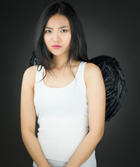 Serious Asian young woman dressed up as an angel looking angry