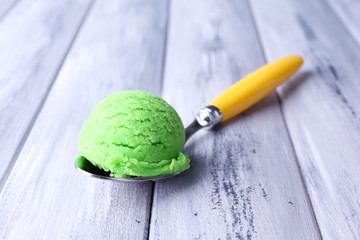 Spoon with tasty ice cream ball on color wooden background