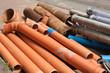 Rohre aus Kunststoff und Metall liegen am Strassenrand