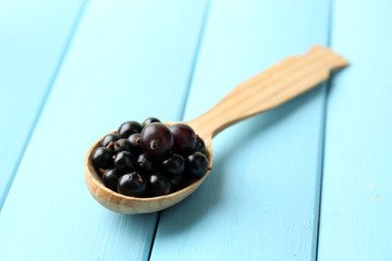 Ripe blackcurrants in wooden spoon on color wooden background.