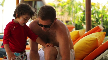 Father putting sunblock on sons legs, steadycam shot