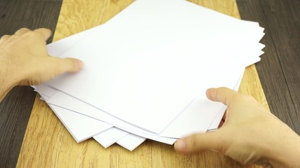 Man organise empty white paper size A4 on wood background