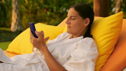 Woman lying on bed and typing on smartphone