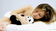 Woman falling asleep with panda plush