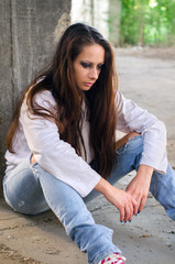 Depressed young girl sitting on the concrete floor