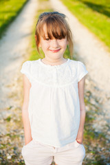 Outdoor portrait of a cute little girl on a nice summer evening