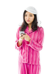 Sad young Asian woman text messaging on a mobile phone