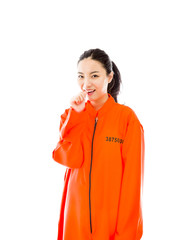 Young Asian woman smiling in prisoners uniform with finger in