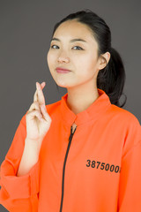 Young Asian woman in prisoners uniform with finger crossed