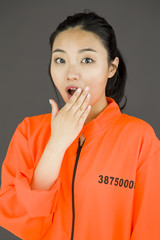 Young Asian woman with shocked expression in prisoner uniform