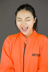 Young Asian woman shouting in excitement and wearing prisoners