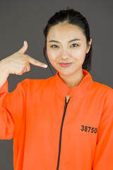 Young Asian woman pointing herself in prisoners uniform