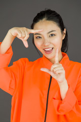 Young Asian woman making frame with fingers in prisoners uniform