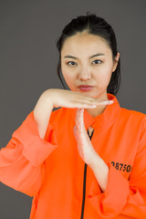 Young Asian woman making time out signal with hands in prisoners
