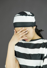 Upset young Asian woman with her head in hands in prisoners