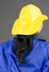 Back view of a lady firefighter in blue protective suit wearing