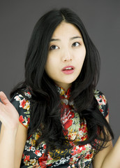 Asian young woman don't know what to do isolated on colored
