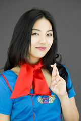 Asian air stewardess crossing her fingers