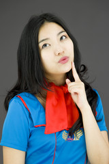Asian air stewardess looking up with finger on chin