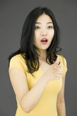 Shocked Asian young woman with pointing