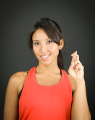 Young woman showing her fingers crossed and smiling