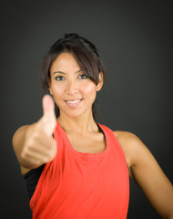 Portrait of a young woman smiling with showing thumb up sign