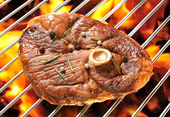Grilled meat on the flaming grill ( lamb leg )