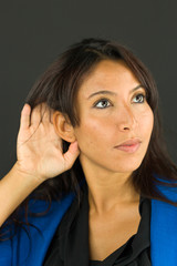 Close up of a young businesswoman hand to ear listening