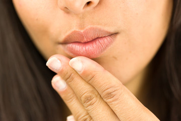 Extreme close-up of a young woman day dreaming with hand on chin