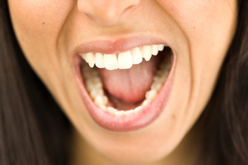 Extreme close-up of a young woman shouting with mouth open
