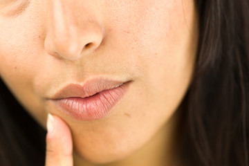 Extreme close-up of a young woman day dreaming with finger on