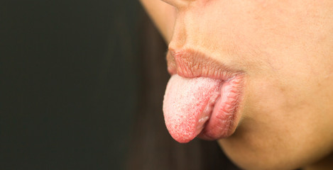 Extreme close-up of a young woman sticking her tongue out