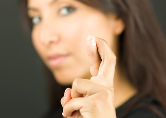 Extreme close-up of a young woman showing her fingers crossed