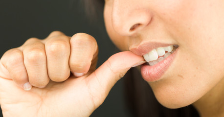 Extreme close-up of a young woman biting her nails and smiling