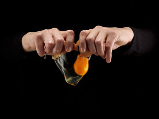 Hands breaking an egg