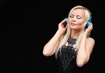 Blonde Girl with Headphones Enjoying the Music over Black