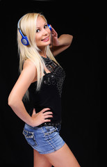 Blonde Girl with Headphones over Black Background. Happy