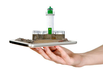 Man is showing white lighthouse with green details