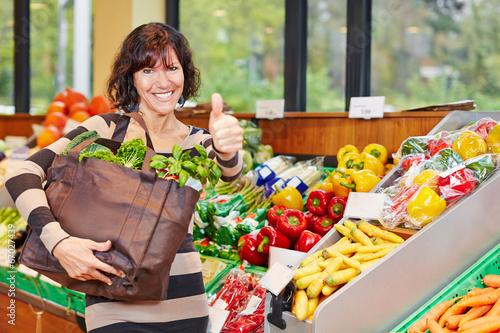 Frau im Biomarkt hält Daumen hoch - 67027439